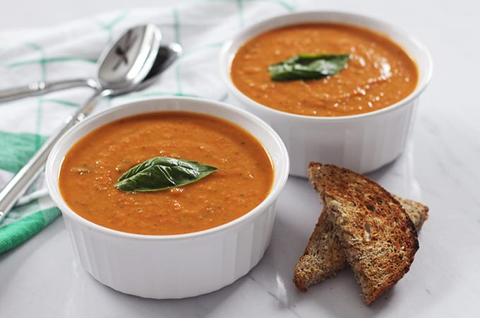 This delicious bowl of creamy tomato basil soup will warm you up on any chilly day! The soup is vegan and gluten-free and is made with a secret vegan ingredient to make it creamy!