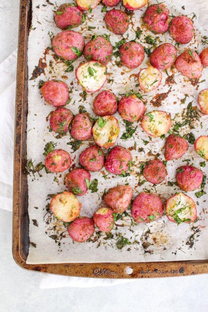 roasted and seasoned radishes on a sheet pan