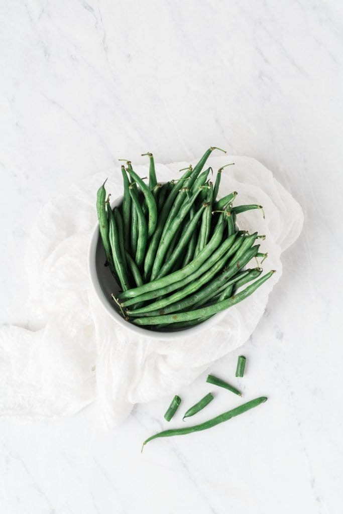bunch of asparagus in a bowl on marble counter